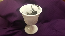image of white cup of dark gray ashes on purple cloth